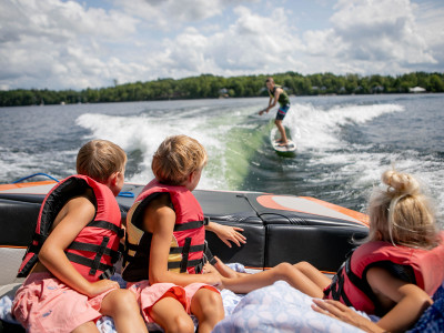 Kids on boat watching wakesurfer